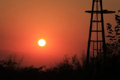 Firey Windmill Sunset Silhouette. A Windmill shot closeup with a Firey Sunset. With Silhouette's that's bright and colorful shot in Kansas Stock Image