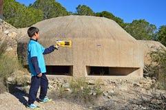 Firing A Nerf Gun. A boy firing a bullet from a toy gun outside a war bunker Royalty Free Stock Photography