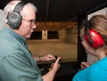 Firing Range Instruction. Student with instructor on pistol firing range Stock Photo
