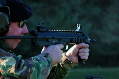 Firing in shades. A sailor firing a machine gun on the range and wearing sunglasses Stock Image