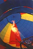 Firing Up Hot Air Balloon. Close up shot of the interior of a hot air balloon as the flame causes the fabric to expand. Red, blue, yellow, orange and navy Royalty Free Stock Image
