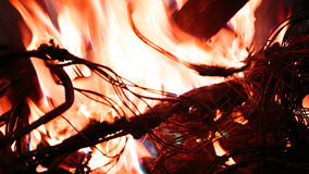 Firing wire in fire. Wires on fire. Firing winding insulation of electrical wiring in the fire close-up Stock Photo