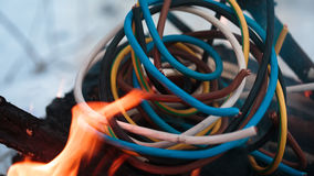 Firing wire in fire. Wires on fire. Firing winding insulation of electrical wiring in the fire in the winter woods Stock Image
