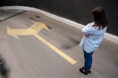 Firl που στέκεται σε δύο βέλη που τυπώνονται κοντά στο δρόμο grunge, που λαμβάνει την απόφαση Στοκ Φωτογραφίες