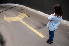 Firl standing near two arrows printed on grunge road, making decision. Business concept Stock Photos