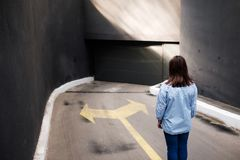Firl standing near two arrows printed on grunge road, making decision. Business concept Stock Image