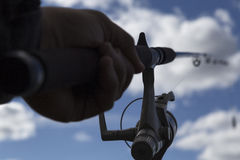 In a firm grip. A hand and a fishing rod toward a clody and blue sky stock photos