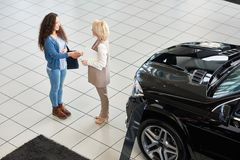 Firm Handshake of Customer and Consultant. High angle view of smiling curly customer shaking hand of blond-haired consultant after successful deal in car Stock Photos