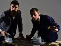 Firma angażująca w bezprawnym biznesie Mężczyzna przy stołem z stosami pieniądze i alkoholu napoje Bezprawny biznesowy pojęcie obraz stock