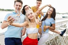 Firma atrakcyjni przyjaciele śmia się żółtych koktajle, pije, uspołecznia selfie w ładnym i robi obraz stock