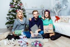 Firma chłopiec i dwa dziewczyny siedzi blisko choinki wewnątrz Zdjęcia Stock