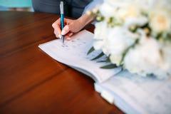 Firma de la novia en la ceremonia que se casa fotos de archivo