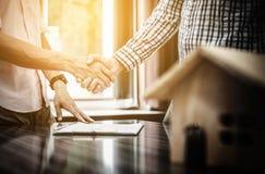 Firma de un contrato de las propiedades inmobiliarias entre el comprador y el agente Imagen de archivo libre de regalías