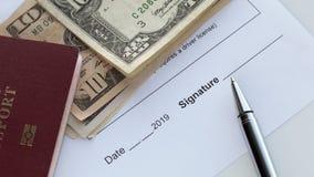 Firma de un documento Espacio para firmar Pasaporte rojo con los billetes de banco del dólar americano imágenes de archivo libres de regalías