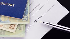 Firma de un documento Pasaporte azul con euro fotos de archivo libres de regalías