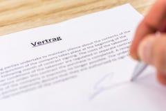 Firma di un contratto con la parola tedesca per il contratto nel titolo fotografia stock libera da diritti