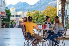 Firma dziewczyny siedzi w plenerowej miasto kawiarni na ulicie zdjęcie royalty free