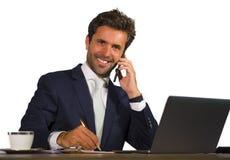 Firma korporacyjny odosobniony portret młody przystojny i atrakcyjny biznesmen pracuje przy biurowym biurkiem opowiada na telefon fotografia stock