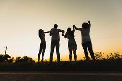 Firma młode dziewczyny i faceci stoimy na trawie blisko drogi na letnim dniu i trzymamy ich ręki fotografia royalty free