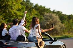 Firma młode kobiety i faceci robimy selfie w czarnym kabriolecie na drodze na ciepłym słonecznym dniu obrazy stock