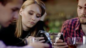 Firma młodzi ludzie jest przyglądająca ich telefony komórkowi w barze zbiory