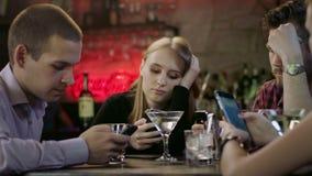 Firma młodzi ludzie jest przyglądająca ich telefony komórkowi w barze zbiory wideo