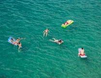Firma młodzi ludzie na lotniczych materac w morzu fotografia royalty free