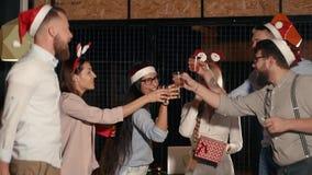 Firma młodzi przyjaciele świętuje boże narodzenia, klika szkło z alkoholem zdjęcie wideo