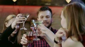 Firma młodzi przyjaciele clinking szkła w barze zbiory