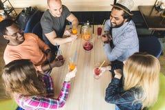 Firma m?odzi ludzie ma zabaw?, pije napoje, koktajle, soki w kawiarni spotkanie najlepsi przyjaciele obraz stock