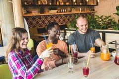 Firma m?odzi ludzie ma zabaw?, pije napoje, koktajle, soki w kawiarni spotkanie najlepsi przyjaciele obrazy royalty free