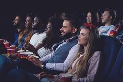 Firma międzynarodowi ludzie ogląda film w kinie zdjęcia royalty free