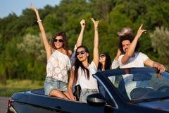 Firma piękne młode dziewczyny i faceci jesteśmy uśmiechnięci i pozycje w czarnym kabriolecie na drogowym mieniu ich ręki zdjęcie royalty free