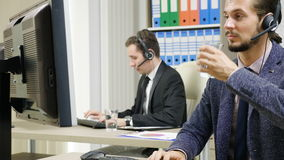 Firma pracownicy w kostiumu używać słuchawki opowiadać na gorącej linii zbiory wideo
