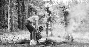 Firma przyjaciele lub rodzinny robi ognisko w lasowym natury tle Przyjaciele pracuje jak drużyna utrzymywać ognisko firma fotografia royalty free