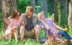 Firma przyjaciele relaksuje przekąski natury pyknicznego tło i ma Firma wycieczkowicze relaksuje przy pyknicznym lasowym tłem zdjęcie stock