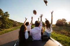 Firma szczęśliwe młode dziewczyny i faceci siedzimy w czarnej kabriolet drodze i rzucamy w górę ich kapeluszy na słonecznym dniu zdjęcie stock
