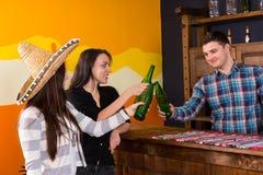 Firma uśmiechnięci młodzi ludzie clinking butelki piwo podczas gdy Obrazy Stock