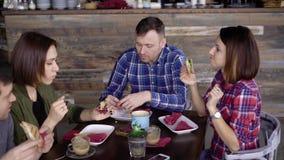 Firma von den Freunden, die am Tisch im Café ihre Mahlzeit genießend und miteinander sprechend sitzen Zwei Männer und zwei Frauen stock video
