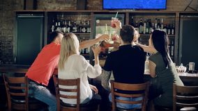 Firma von den Freunden, welche im Restaurant die Geburtstagsfeier klirrt Gläser mit Cocktails feiern Leute, die an sitzen stock footage