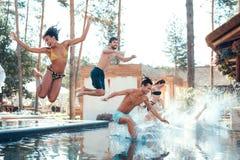 Firma von den glücklichen jungen Leuten, die springen, bei der Poolformung spritzt Schwimmenpool-party-Konzept stockfoto