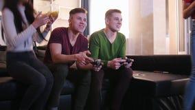 Firma von den jungen Freunden, die zusammen Zeit verbringen Junger Mann zwei, der Spiel spielt, während Mädchen die Nahrung holen stock footage