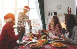 Firma von den netten und glücklichen Freunden, die am Weihnachtsabendessen feiern stockfotos