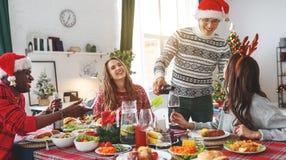 Firma von den netten und glücklichen Freunden, die am Weihnachtsabendessen feiern stockfoto