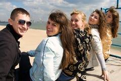 Firma von fünf jungen Leuten, die zusammen sitzen Lizenzfreies Stockfoto
