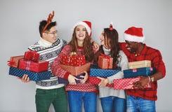 Firma von glücklichen Freunden mit Weihnachtsgeschenken an der leeren Wand lizenzfreies stockbild