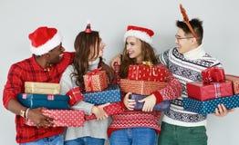 Firma von glücklichen Freunden mit Weihnachtsgeschenken an der leeren Wand lizenzfreie stockfotografie