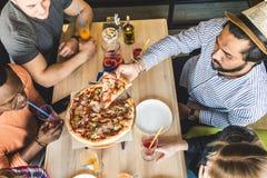 Firma wielokulturowi m?odzi ludzie w cukiernianej ?asowanie pizzy, pij?cy koktajl, mie? zabaw? obrazy royalty free