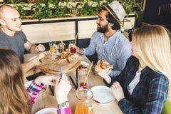 Firma wielokulturowi m?odzi ludzie w cukiernianej ?asowanie pizzy, pij?cy koktajl, mie? zabaw? zdjęcie stock