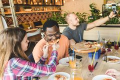 Firma wielokulturowi m?odzi ludzie w cukiernianej ?asowanie pizzy, pij?cy koktajl, mie? zabaw? zdjęcia royalty free